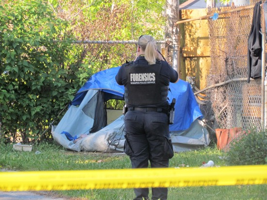 An officer from the forensic unit takes photographs of a tent after the death of man at William Whyte Park on Wednesday morning. (Photo: Northern Plains Freelancer)