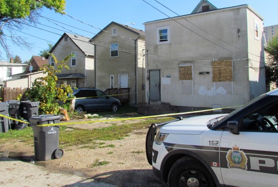 A police vehicle is parked in the alley behind a house on Balmoral Street where a dead woman was found inside. Photo: Northern Plains Freelancer.