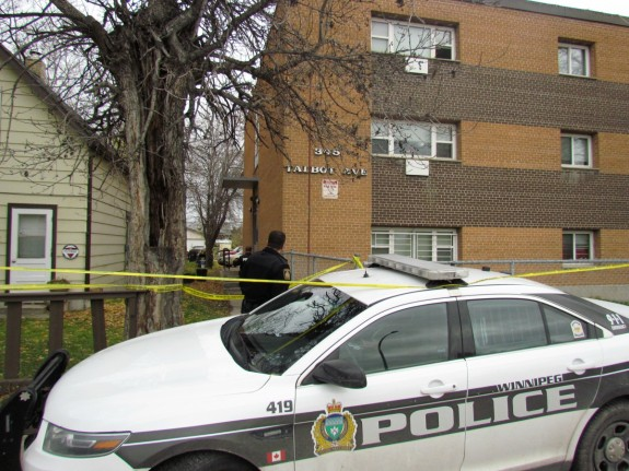 A police officer stands outside an apartment building on Talbot Avenue after a fatal stabbing on Wednesday morning. Photo: Northern Plains Freelancer.