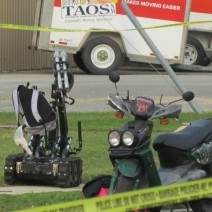 A bomb-disposal robot holds onto a backpack.