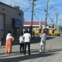 Worried parents look at a school bus after the driver crashed into a pole.